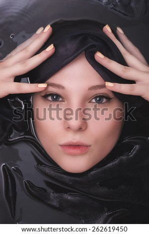 Fashion portrait of young woman floating in Spa filled with cloth - stock photo