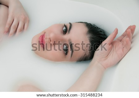 Fashion portrait of young woman floating in Spa filled with milk - stock photo