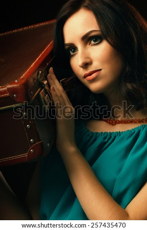 Fashion portrait of young woman holding vintage suitcase. Wanderlust concept - stock photo