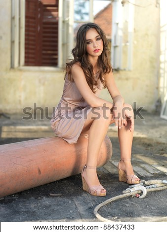 fashion portrait of young woman, in an old house, in ruin, sitting on an old pipe