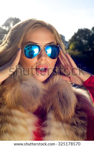 Fashion portrait of young woman wearing red dress,blue sunglasses and fur vest.Young attractive blonde wearing stylish sunglasses.bright picture of teenage girl with expression of surprise     - stock photo