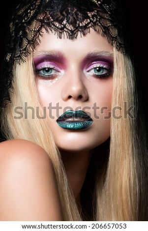 Fashion portrait of young woman with blue lips and wet eyelid effect stage make-up
