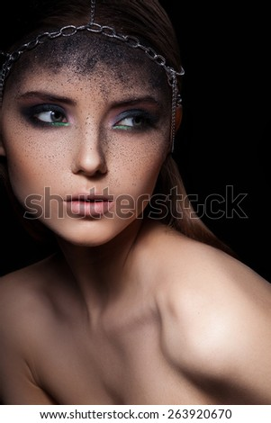 Fashion portrait of young woman with dark dusty make up and  head accessory of chains