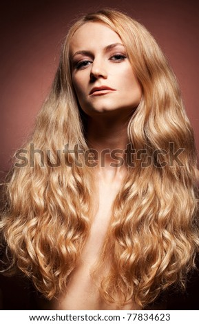 Fashion portrait of  young woman with long hair on brown background - stock photo