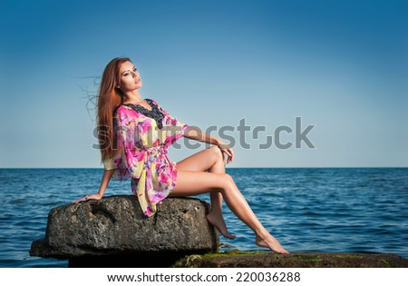 Fashion portrait of young woman with long red hair hair in a colored blouse at the beach. Sensual attractive girl on a rock near the sea. Woman with perfect body relaxing on the rock near the ocean - stock photo