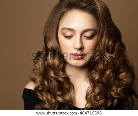 Fashion portrait of young woman with magnificent curly hair. Brunette girl. Perfect make-up.