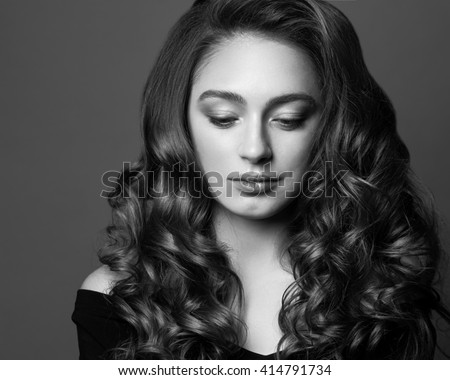 Fashion portrait of young woman with magnificent curly hair. Brunette girl. Perfect make-up. Black and white photo.