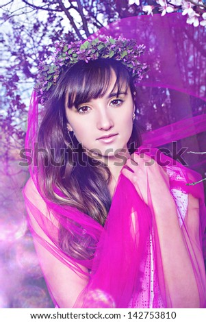 Fashion portrait of young woman with pink shawl and floral wreath