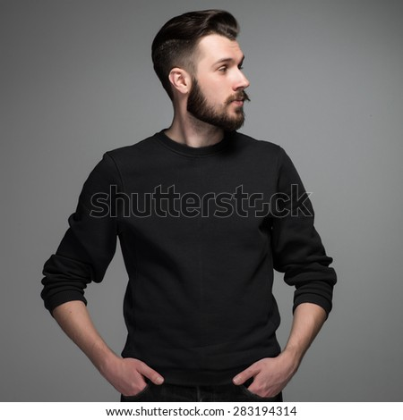 Fashion portrait ofprofile of  young man in black  poses over gray background. look toward - stock photo