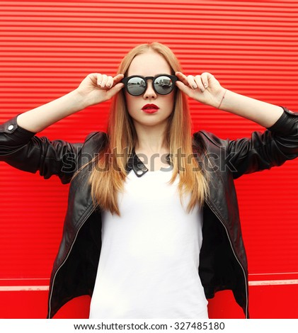 Fashion portrait pretty stylish woman with red lipstick wearing a rock black jacket and sunglasses in city - stock photo