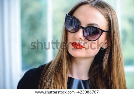 Fashion portrait stylish pretty woman in sunglasses outdoor. Young woman wearing a rock black style having fun in city. Street fashion. Red lipstick.