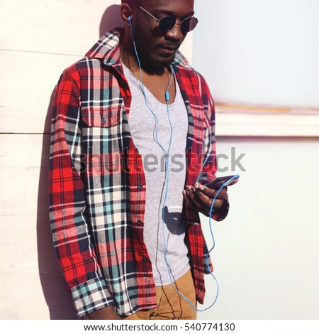 Fashion portrait young african man listens to music on the smartphone, hipster wearing a plaid red shirt and sunglasses over city background.