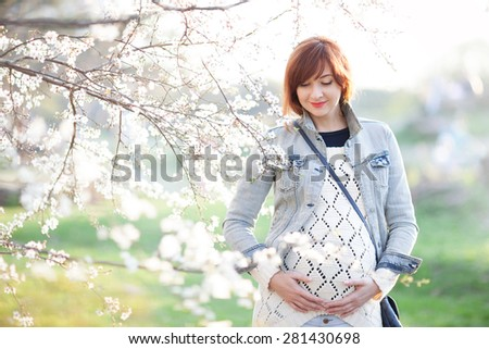Fashion pregnant woman enjoying of the spring blooming - stock photo