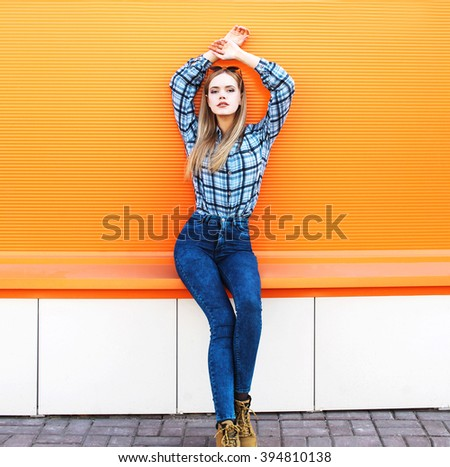 Fashion pretty blonde girl model over colorful orange background - stock photo