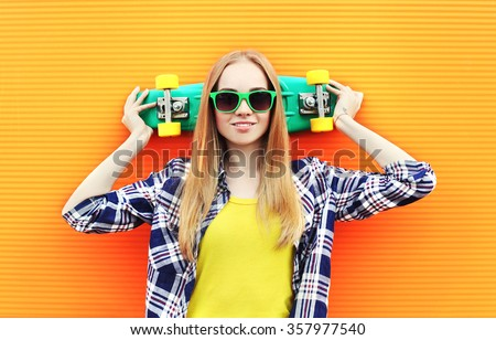 Fashion pretty blonde girl wearing a sunglasses with skateboard having fun over colorful background - stock photo