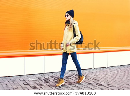Fashion pretty blonde woman walking in city over colorful orange background - stock photo