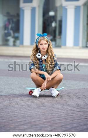Fashion pretty cool girl wearing a blue clothes, headphones and skateboard in city