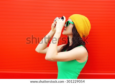 Fashion pretty cool girl wearing a colorful clothes with old retro camera shooting in the city  - stock photo