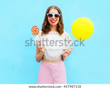 Fashion pretty smiling woman with air balloon and lollipop over colorful blue background - stock photo