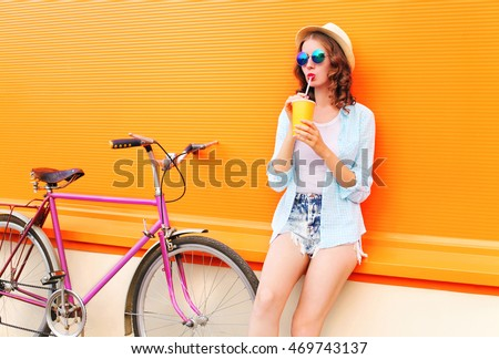 Fashion pretty woman drinks fruit juice from cup with retro bicycle over colorful orange background