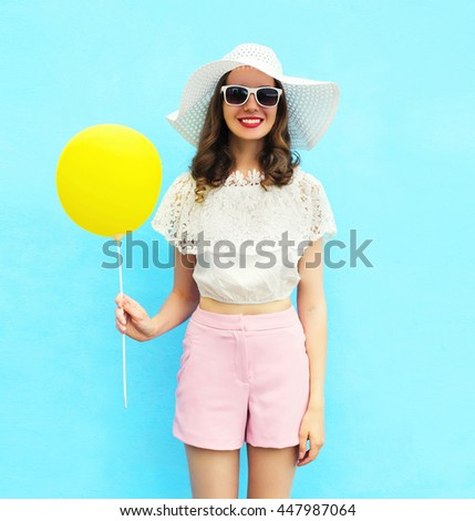Fashion pretty woman in straw hat with air balloon over colorful blue background - stock photo