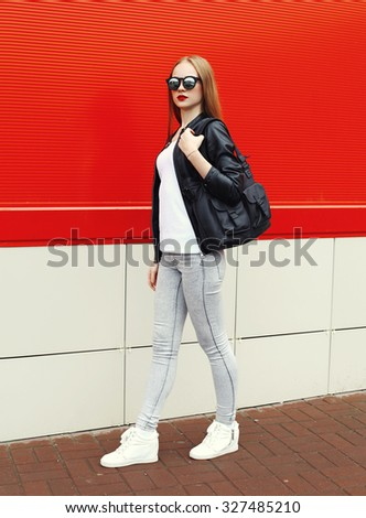 Fashion pretty woman wearing a rock black leather jacket, sunglasses and bag walking in city over red background - stock photo