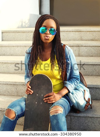 Fashion pretty young african woman with skateboard in colorful clothes and sunglasses having fun - stock photo