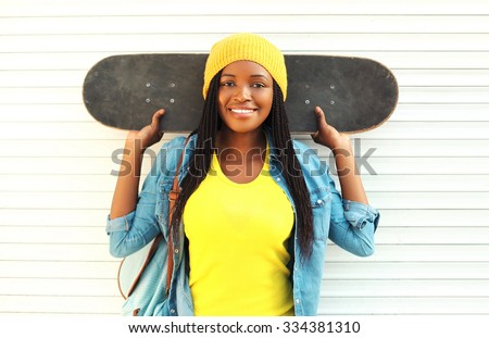 Fashion pretty young smiling african woman with skateboard in colorful clothes over white background - stock photo