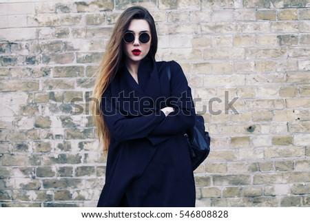 Fashion pretty young woman model in total black style stands over brick wall background. Outdoor portrait of cute blonde girl having fun, urban city street, long hairs, bright make up.