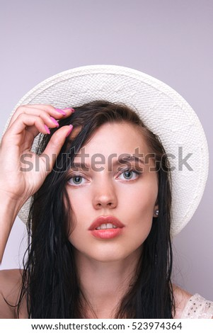 Fashion pretty young woman wearing a white straw hat in studio on a grey background