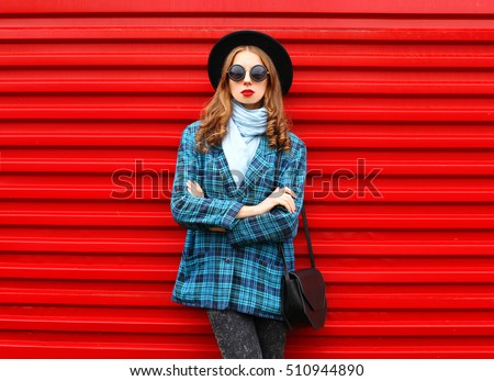 Fashion pretty young woman wearing black hat coat jacket with handbag over colorful red background
