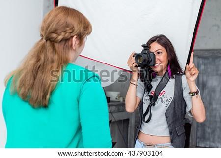 Fashion pro female photographer shooting model in photo studio - stock photo