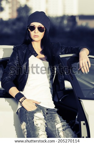 Fashion punk woman in sunglasses standing at the car  - stock photo