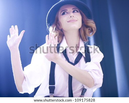 Fashion redhead girl with tie in studio.