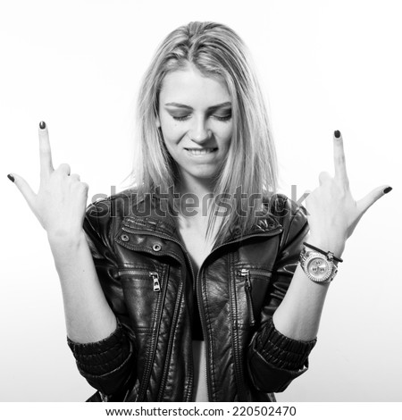 fashion rock star: black and white portrait of sexy young blonde woman in leather jacket posing happy smiling over light copy space background - stock photo
