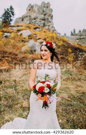 Fashion romantic beautiful bride in luxurious white dress. Smiling young girl with wedding bouquet and head wreath. Rocky landscape as background - stock photo