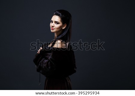 Fashion seductive black hair lady in an elegant fur coat and black underwear on a dark background - stock photo