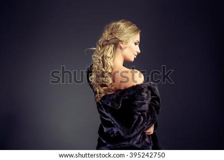 Fashion seductive blond hair lady in an elegant fur coat and black underwear on a dark background - stock photo