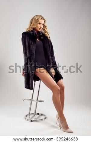 Fashion seductive blond hair lady in an elegant fur coat and black underwear, sitting on the bar stool - stock photo