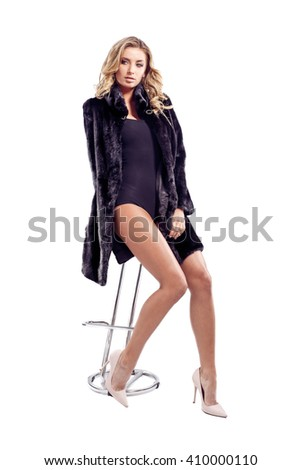 Fashion seductive blond hair lady in an elegant fur coat and black underwear, sitting on the bar stool. Isolated.  - stock photo