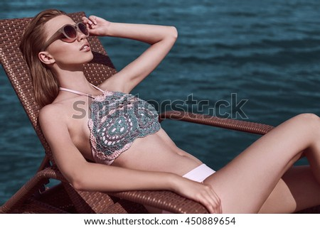 Fashion, seductive girl in knitted swimsuit getting a suntan while lying in the sun chair on the beach. - stock photo