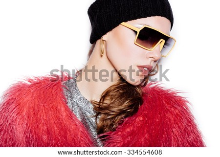 Fashion sexy woman in sunglasses wearing silver dress, pink fur coat, black beanie hat.  White background, not isolated - stock photo