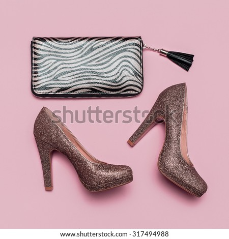 Fashion Shoes and Clutch on pink background. Gold accent