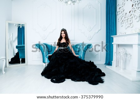 Fashion shoot of beautiful woman in a long black dress in blue room sitting on blue sofa