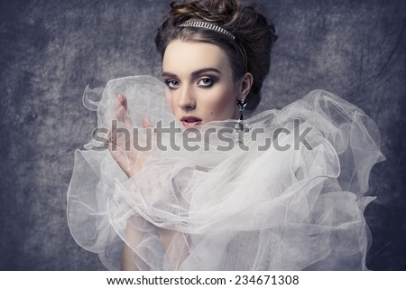 fashion shoot of pretty woman with romantic retro dame style. Wearing baroque dress with frill veil collar, precious earrings and tiara in the hair-style, elegant make-up  - stock photo