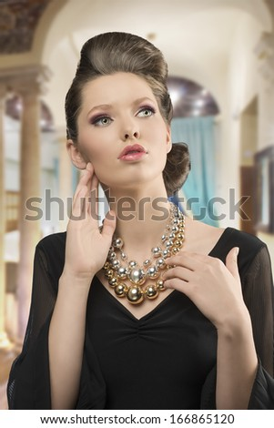 fashion shoot of pretty young brunette girl with elegant style, beautiful hair-style, black dress and big necklace     - stock photo