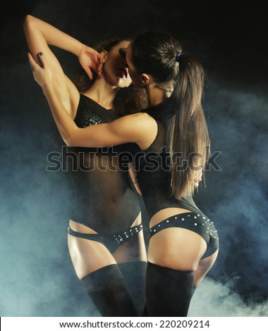 Fashion shoot of two young sexy striptease dancer in club. - stock photo