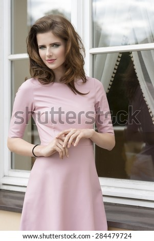 fashion shoot of very pretty brunette woman with natural hair-style, pink dress and stylish make-up, posing outdoor near window  - stock photo