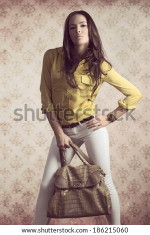 fashion shoot of young sensual girl with brown natural hair-style and modern casual style. taking big vogue bad in the hand