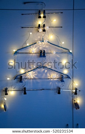 fashion shopping hangers in wardrobe on shelf in shape on christmas or xmas tree with celebration - Christmas Lights Hangers